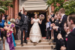 the stone couple cheering and coming out of the church doors to a crowd and bubbles